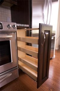 Close-up after photo of the custom made pull-out spice rack we nestled between the stove and fridge.