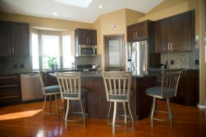 Open kitchen with kitchen island. Custom walnut shaker cabinets and drawers throughout