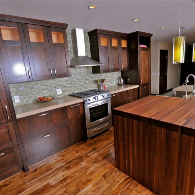 Beautiful walnut Shaker-style kitchen cabinets and kitchen island by Evolve Kitchens with dark wood grain emphasized by stainless steel appliances