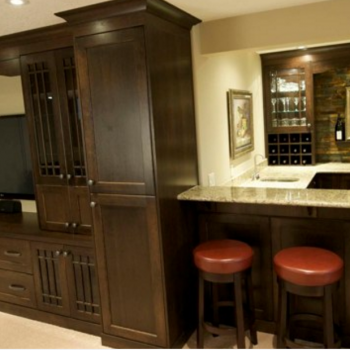 Dark wood custom bar cabinets, granite countertop and full wall entertainment unit custom made by Evolve Kitchens