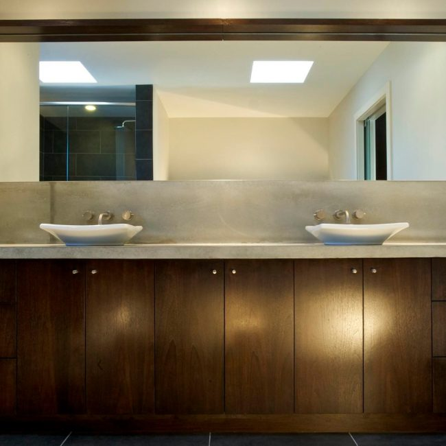 Custom bathroom cabinets in dark brown with stainless handles, made and installed by Evolve Kitchens of Calgary