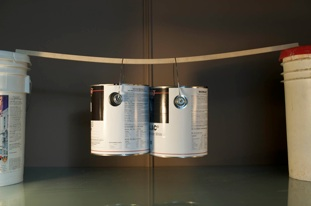 Photo of 2 full paint cans hanging from single piece of the cabinetry boarding that Evolve Kitchens uses to prove material strength