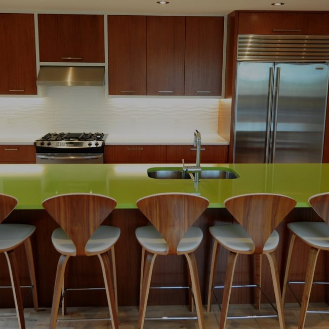 Kitchen island with stunning green countertop and modern stainless steel sink and faucet by Evolve Kitchens