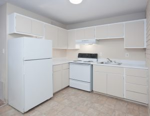 Drab old white cupboards in an open kitchen